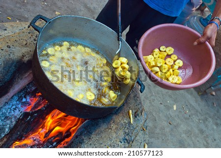 fried plantains banana in pan on open fire preparation - stock photo