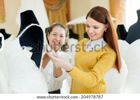 Friendly shop consultan helps the bride in choosing bridal gown at shop of wedding fashion. Focus on girl - stock photo