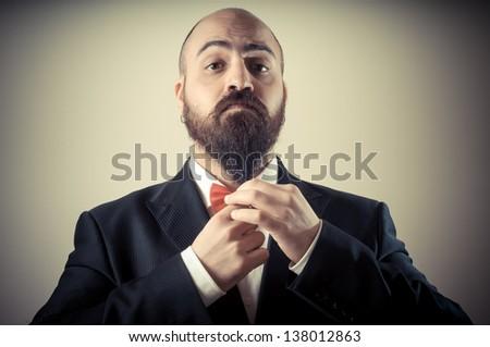funny elegant bearded man touching beard on vignetting background - stock photo