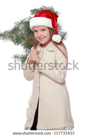 funny little girl with blond hair in a red Santa hat holding a bush natural pine/Positive young girl in Santa's hat is happy and laughing with Christmas tree - stock photo