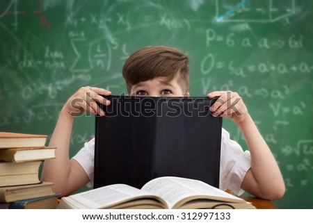 Funny schoolboy hiding behind book sitting in a classroom over a blackboard - stock photo