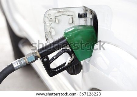 Gas pump nozzle in the fuel tank of a white car. - stock photo
