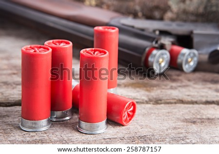 12 gauge shotgun shells with shotgun on wood surface - stock photo