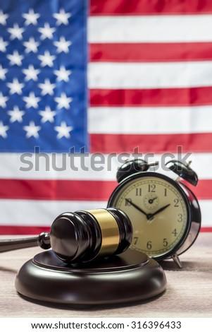 Gavel and Alarm Clock, American flag background - stock photo