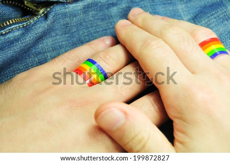 Gay marriage concept with hands and rainbow rings - stock photo