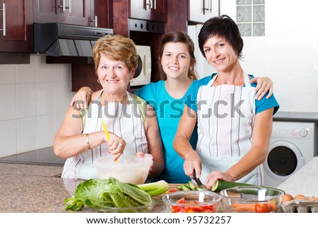 3 generation family cooking in kitchen - stock photo