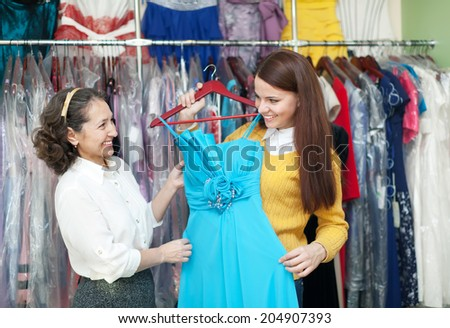 girl chooses evening dress at clothing boutique. Cconsultant helps her - stock photo
