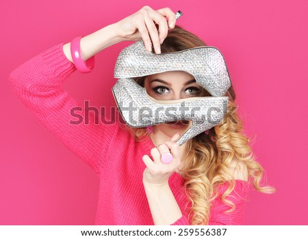girl holding a silver high heel shoe in her hands - stock photo