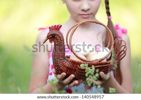 girl holding basket of raw eggs/Cute young girl standing in the tall grass outdoors - stock photo