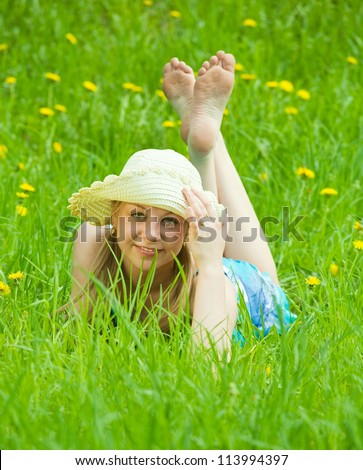 girl in hat lying in meadow grass - stock photo
