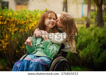 girl in wheelchair with  girlfriend smiling into the camera in the park on spring day - stock photo