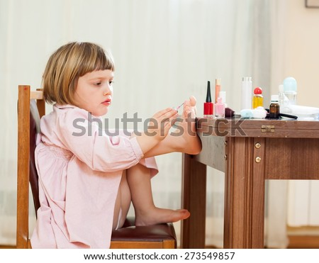 girl paints her nails on  feet - stock photo