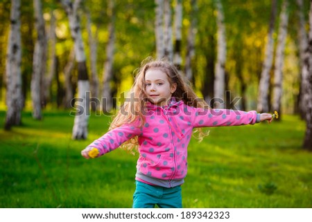 girl running in the park. Wind blows hair. Happiness, smile, summer - stock photo