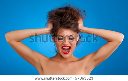 girl screaming and pulling her hair over blue background - stock photo