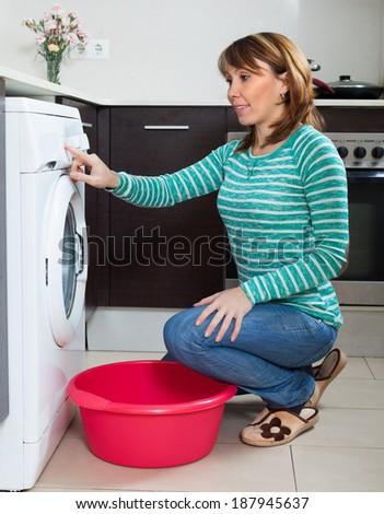 girl using washing machine at home - stock photo