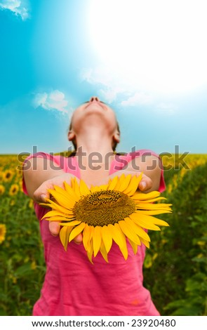 girl with a sunflower against the sky - stock photo