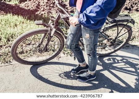 girl with bike walks on path by the city street sidewalk - stock photo
