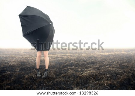girl with umbrella on black field - stock photo
