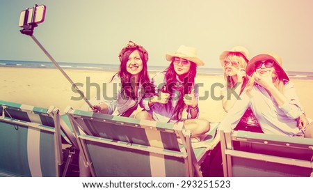 4 girls interracial best friends on beach taking self portrait using a selfie-stick. Happy girls smiling and making funny faces and mustache with hair retro vintage filter and custom white balanced - stock photo