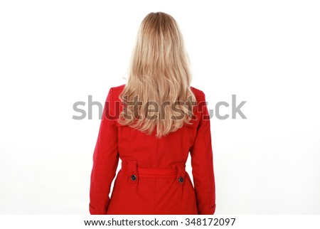 glamorous, beautiful blonde young woman with blonde hair, wearing  long, red winter trench coat.   3/4  portrait,  back view. isolated on white background. - stock photo