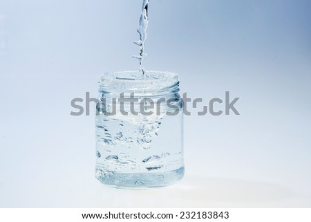 glass jar on blue background with pouring water - stock photo