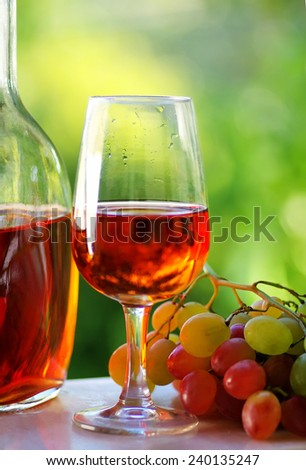 Glass of rose wine and grapes - stock photo