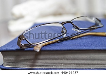 Glasses and blue book. Reading, learning books.  - stock photo