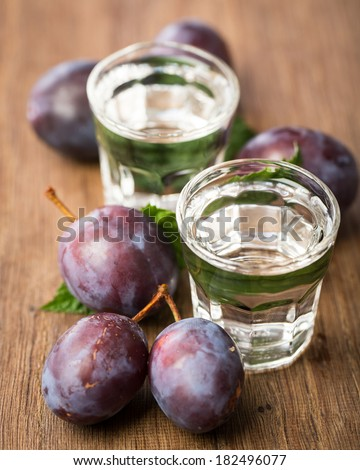 2 glasses of plum brand with plums on wooden board - stock photo