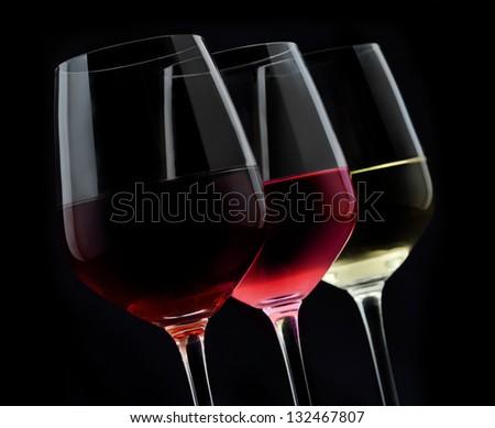 3 glasses of wine in dark background - stock photo
