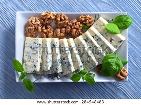 gorgonzola cheese with basil and walnuts on blue wooden table - stock photo