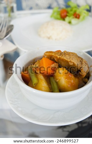 Goulash/ Pork stew with potatoes, carrots and peas  in white bowl  served with steamed rice on the table - stock photo