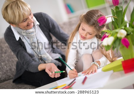 Grandmother helping granddaughter with homework at home - stock photo