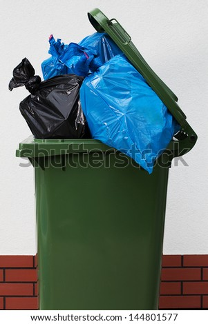 Green garbage can over a white background with a plastic - stock photo