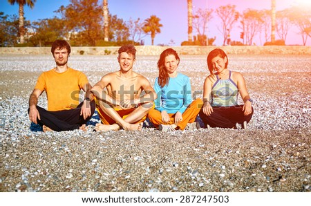 group of friends on the beach at the sunrise. - stock photo