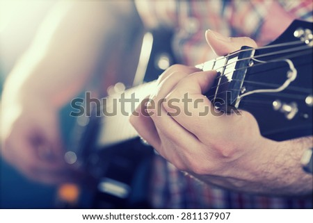 Guitarist on stage in the stage light - retro styled photo - stock photo