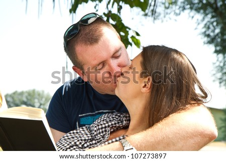 Guy and girl with books on the nature near lake - stock photo