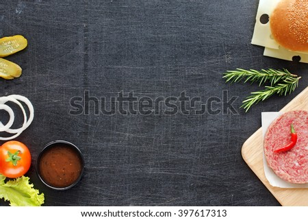 Hamburger ingredients. Homemade minced beef with chili and herbs, sesame bun, onion rings, pickle, tomato, lettuce, hot BBQ sauce on a black wooden background. - stock photo