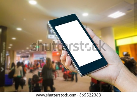 Hand Checking-In For A Flight Using Cellphone, hand holding mobile phone with flight mode in the airplane,phone in the hand with a blank screen and blurred a plane airport in the background  - stock photo