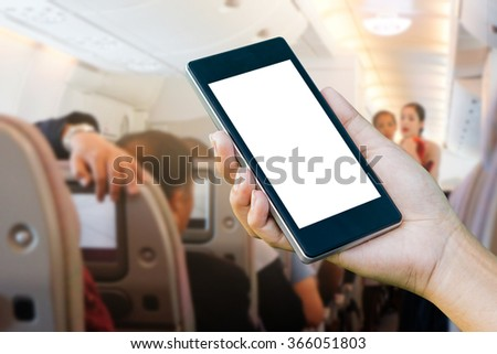 Hand Checking-In For A Flight Using Cellphone, hand holding mobile phone with flight mode in the airplane,phone in the hand with a blank screen and blurred a plane in the background - stock photo