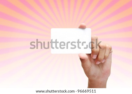 hand holding business card on rays of light pink background. - stock photo