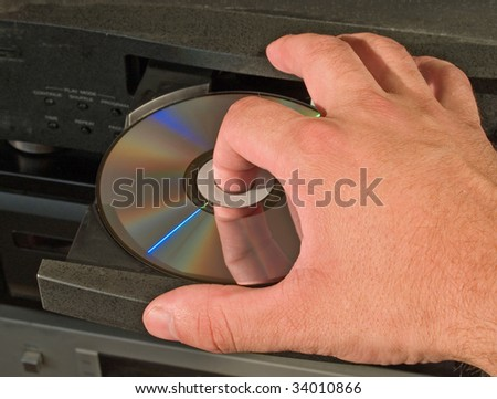 hand inserting musical disk in player - stock photo