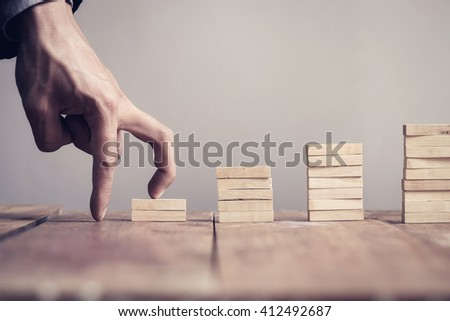 Hand of business man step up to a toy staircase to success target. Vintage tone. - stock photo