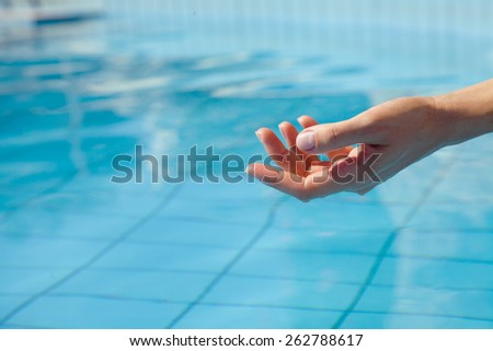 Hand resting girl on a background of blue water pool - stock photo