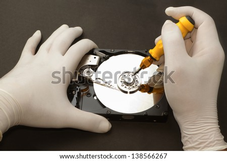 Hand with gloves repairs hard drive ,data recovery concept - stock photo