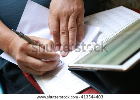 hand write pen on document paper with tablet - stock photo