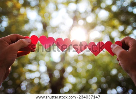 hands holding a string of paper hearts up to the sun during sun - stock photo