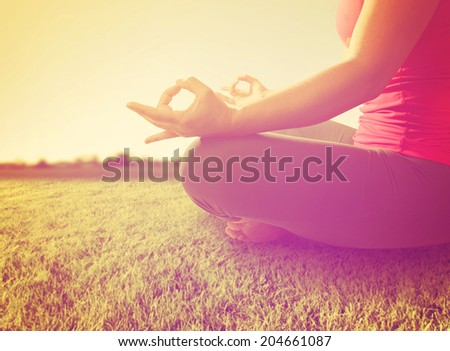 hands of a woman meditating in a yoga pose on the grass toned with a soft instagram like filter - stock photo