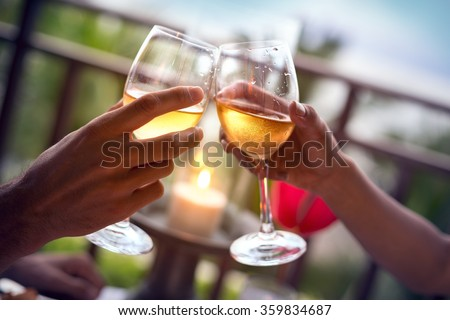 Hands of man and woman cheering with glasses of white wine  - stock photo