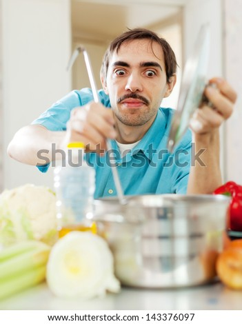 handsome guy tasting veggie soup with ladle from pan in kitchen - stock photo