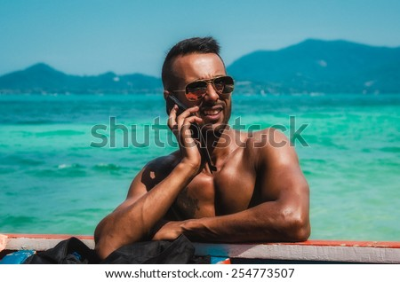 handsome middle eastern man talking on the  phone in a tropical sea - stock photo